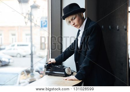 Pretty blonde young girl talking on the phone in cafe