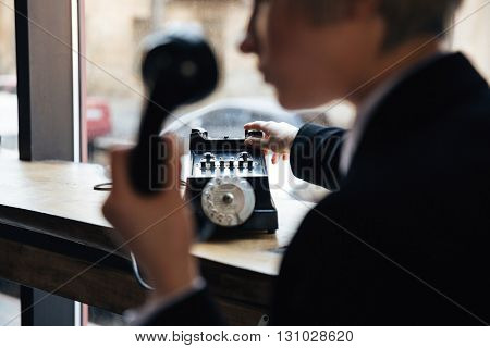 Cropped image of young beautiful woman with retro telephone in cafe