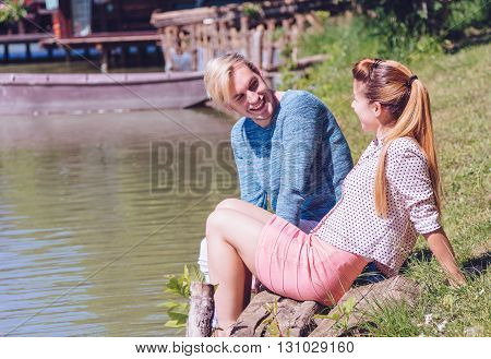 Funny couple laughing and looking each other outdoors with unfocused background