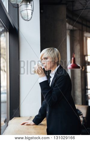 Stylish pretty blonde girl standing at the windowsill and drinking in cafe