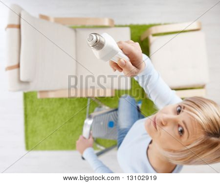 Woman in high angle view trying to change light bulb standing on ladder in living room looking up.Focus placed on light bulb.