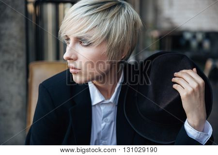 Closeup portrait of a beautiful stylish girl in cafe holding hat