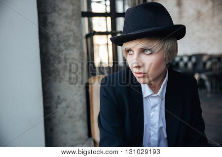 Closeup portrait of a beautiful stylish girl in hat in cafe