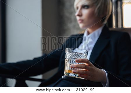 Stylish blonde girl sitting in chair in cafe with glass of whiskey