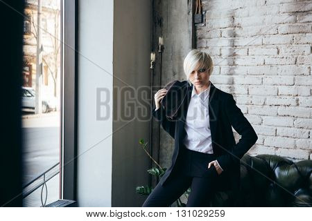 Blonde stylish girl relaxing on the couch and holding a hat in a cafe