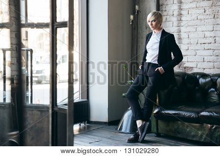 Blonde cute girl standing near the couch in a cafe with her legs crossed