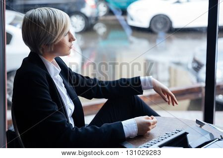 Pretty blonde girl thinking about something in cafe using typewriter, street reflection in window
