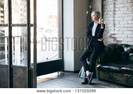 Beautiful blonde girl holding a glass of whiskey in a bar and waiting for somebody