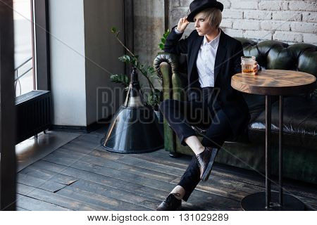 Blonde hipster girl sitting on a couch with her legs crossed in a cafe