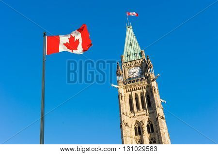 Close up of peace tower (parliament building) with a big canadian flag over blue sky in Ottawa Canada