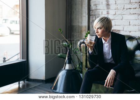 Stylish blonde girl drinking alcohol in a modern cafe