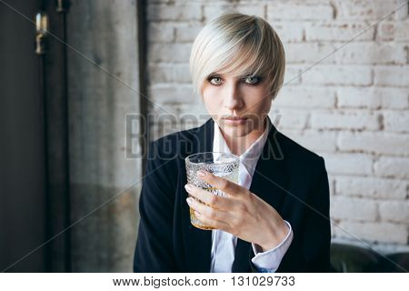 Stylish pretty blonde girl holding a glass of alcohol drink in a bar