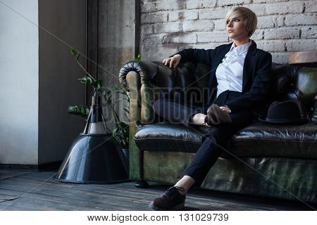 Stylish blonde girl sitting on the leather couch and thinking about something