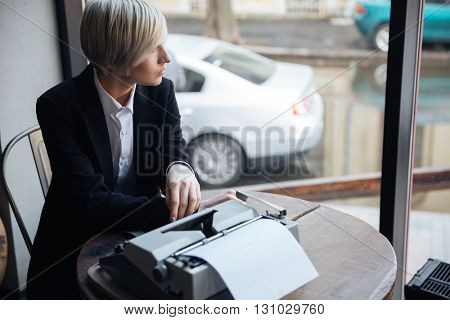 Beautiful blonde girl sitting at the table in cafe