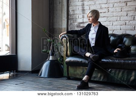 Stylish blonde girl sitting on the leather couch with her legs crossed