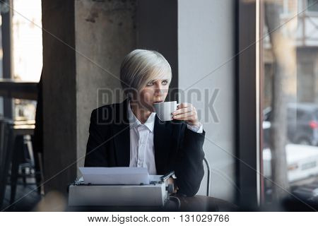 Beautiful blonde girl siting in a modern cafe with a cup of coffee