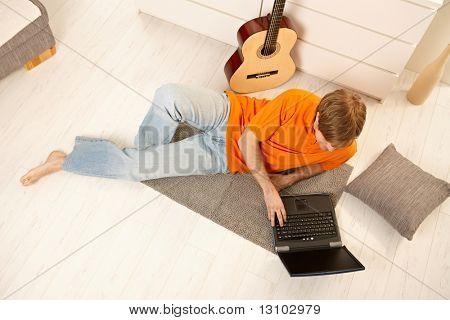 Junger Mann liegend am Boden des Wohnzimmers neben Gitarre, mit Computer, high Angle View entnommen.