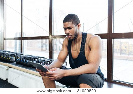 Healthy fitness man using tablet computer in the gym while resting