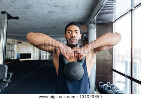 Healthy fitness guy doing workout using heavy kettlebell in the gym
