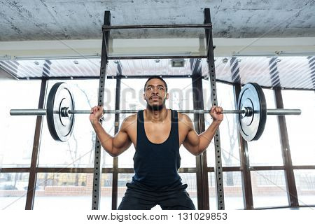 Muscular weightlifter Doing squats Exercise using barbell in the gym