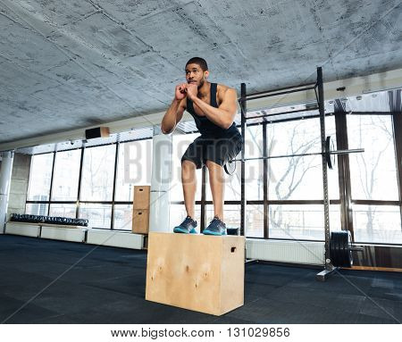 Healthy fitness guy doing exercise with a fit box in a gym
