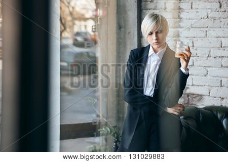 Short haired blonde girl holding a glass of whiskey in a bar