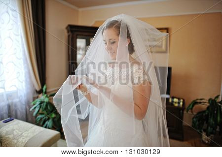 Charming Smiled Bride Under Veil Stay At Room And Looked At Her Hands