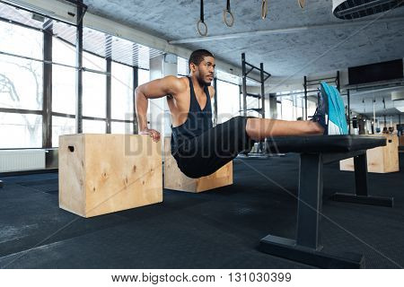 Strong fitness man doing muscles exercises using training apparatus in the gym