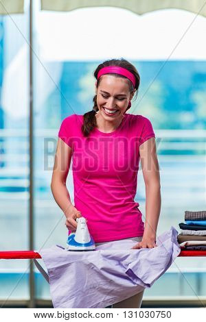 Young woman ironing clothing on board
