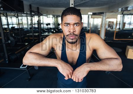 Fitness afro american man resting in the gym after workout and lookind at camera