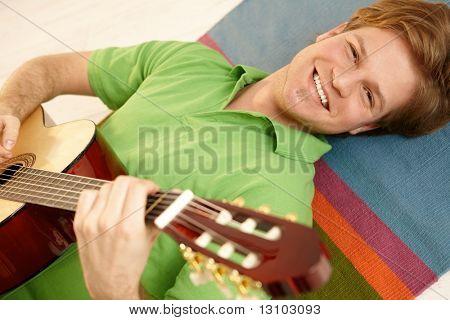 Porträt von handsome Guy Gitarrespielen am Boden liegen.