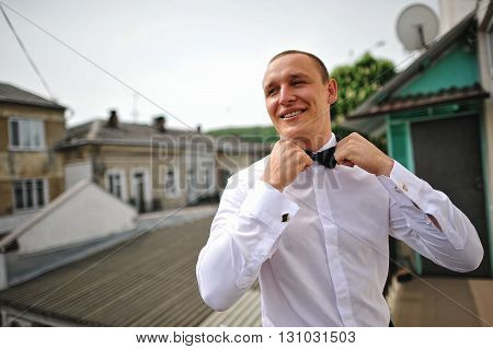 Stylish Groom In A White Shirt And Bow Tie Stay Background Roof. Close Up Portrait Of Man