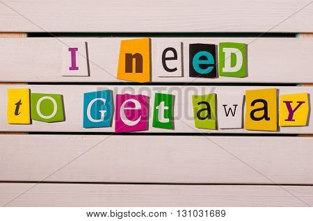 I need get away - written with color magazine letter clippings on wooden board. Summer vacation concept.