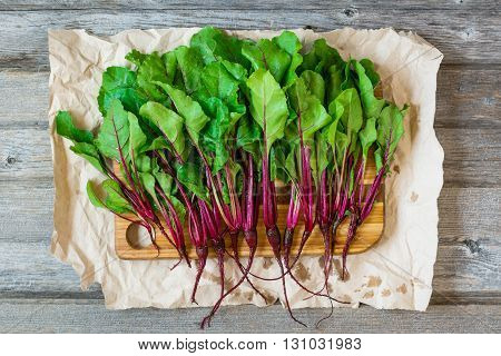 Young fresh beet roots on crumpled craft paper and rustic wooden background.