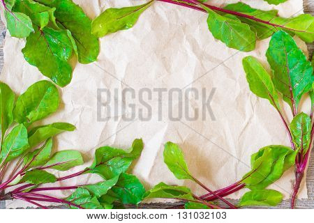 Fresh small beetroots forming a frame on crumpled craft paper for your design.