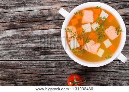 Salmon soup with carrot potatos garnished with dill in white bowl on a dark wooden table top view
