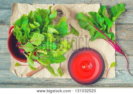 Fresh beets with green leaves in red pot and scattered around on shabby craft paper and wooden background. Knife cap and hemp threads in view. Top view selective focus toned.