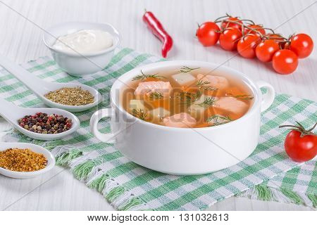 Salmon soup with carrot and potato seasoned with dill in white bowl on a white table with cream sauce and spices close-up