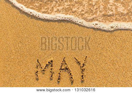 May - written by hand on a golden beach sand.