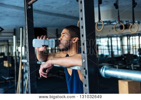 Healthy fitness man drinking water while resting in the gym