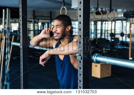 Afro american healthy fitness man using smartphone while resting in the gym