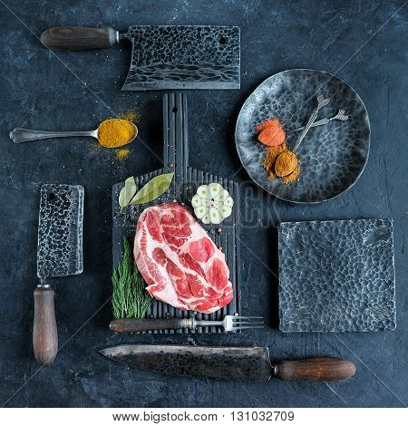 Fresh raw meat on black wooden cutting board surrounded by axes and knives and spices