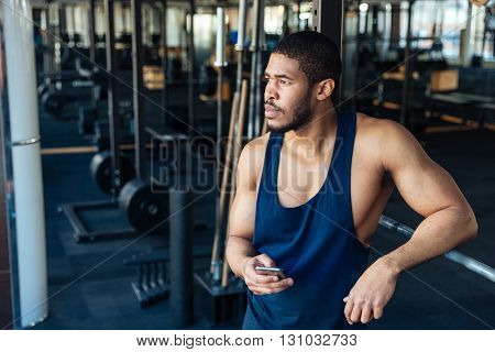 Afro american bodybuilder guy collecting his thoughts after a workout in the gym