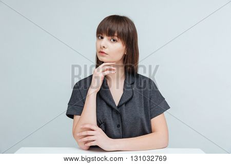 Young brunette woman sitting at the table and looking at camera isolated on a white background
