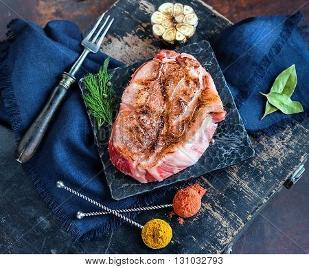Grilled meat slice with salt spices herbs and garlic on metal stand with fork and linen napkin. Grunge wooden background and old dirty metal sheet on the back. Focus on meat slice.