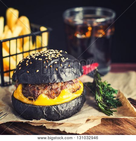 Hot fresh black hamburger with bright yellow cheese and juicy roasted meat on paper with fried potatoes and beverage on the back. Wooden surface. Toned selective focus.