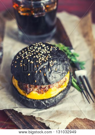 Hot fresh black hamburger with bright yellow cheese and juicy roasted meat on paper with beverage and fork on the back. Wooden surface. Toned selective focus.