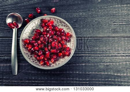 Ripe pomegranate grains on silver saucer and spoon. Dark wooden background. Toned.