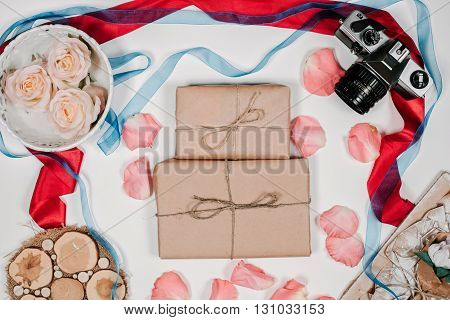 Presents with film camera, vintage white tray, pink rose, red and blue ribbons, pink petals on white background. Top view, flat lay