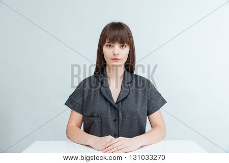 Casual woman sitting at the table and looking at camera isolated on a white background